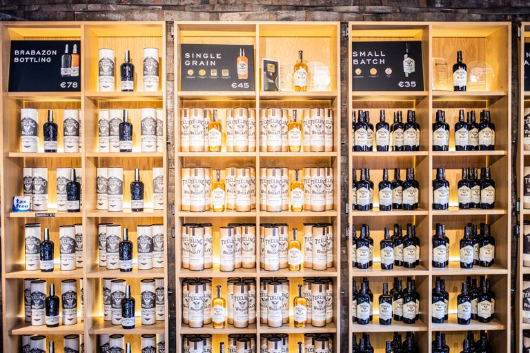 Wooden shelves with assorted whiskey for sale inside Teeling Distillery