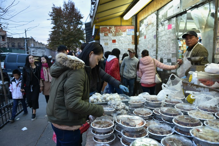A woman browses a street-side seafood market store in Brooklyn's 8th Avenue Chinatown in Sunset Park, New York City.