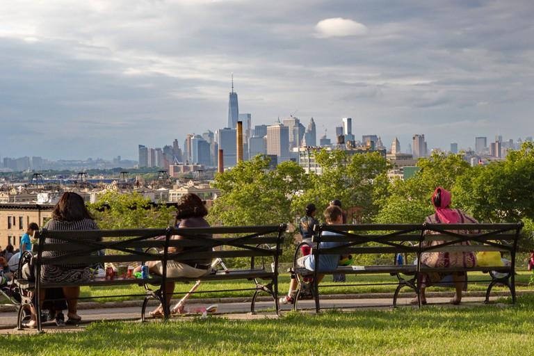 People in Brooklyn's diverse neighborhood of Sunset Park sit on a bench from a high viewpoint and relax and admire view of Manhattan, New York, USA.