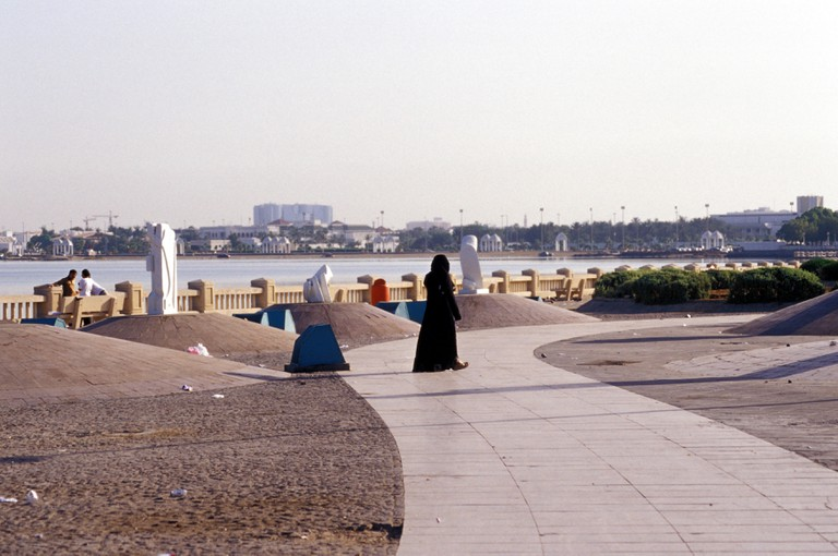 Woman strolling on the Corniche in Jeddah, Saudi Arabia.