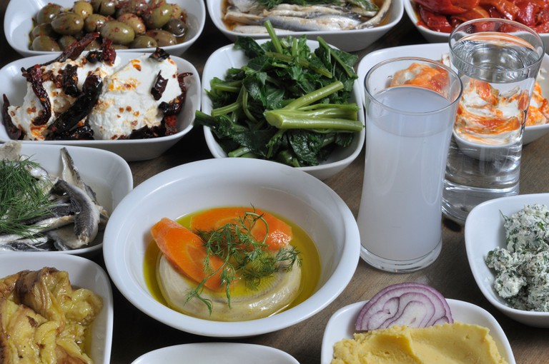 Different kinds of Turkish meze on the dinner table with traditional drink raki.
