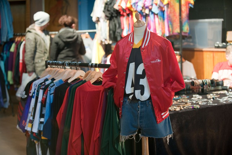 Bright red vintage American teen college jacket on a display at a vintage  fair while a student couple browses a rail of clothes