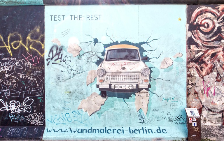 The East Side Gallery is the largest outdoor art gallery in the world.This piece of the wall shows a graffiti of a Trabant car, which breaks through the wall