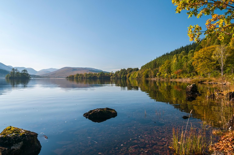 A sunny still autumnal day with the surrounding land and trees reflected in Loch Arkaig, Scotland