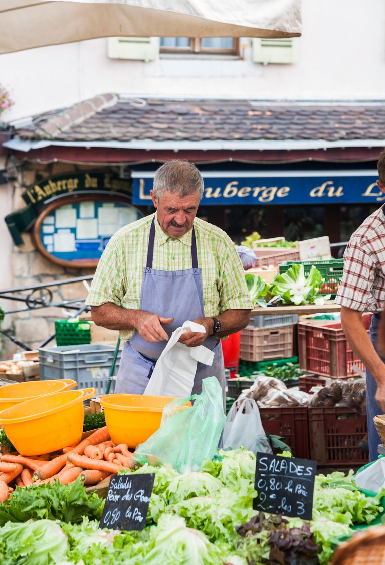 Male stallholder at a vegetable and salad stall at a local outdoor food market in the old town, Annecy, France