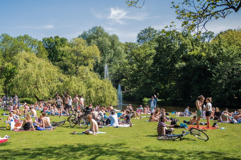 Crowds of people enjoying the sun in Vondelpark, Amsterdam.