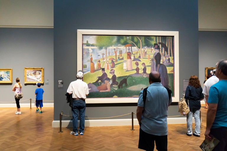Visitors admiring A Sunday Afternoon on the Island of La Grande Jatte ? 1884 by Georges Seurat in the Art Institute of Chicago.