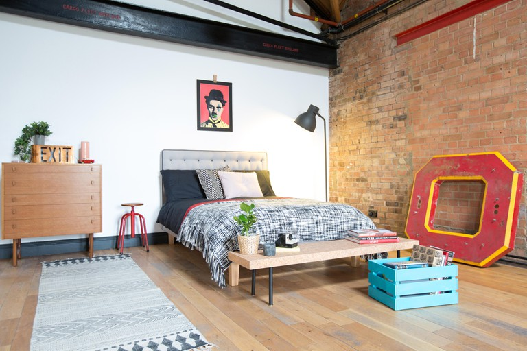 A bedroom in a loft style apartment with exposed brick and midcentury furniture