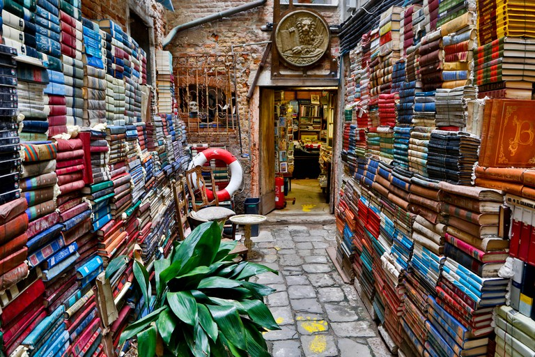 Outside alley bookstore with books stacked high Venice, Italy