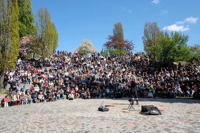 People at Mauerpark on a sunny day watching the open air karaoke show in Berlin, Germany.