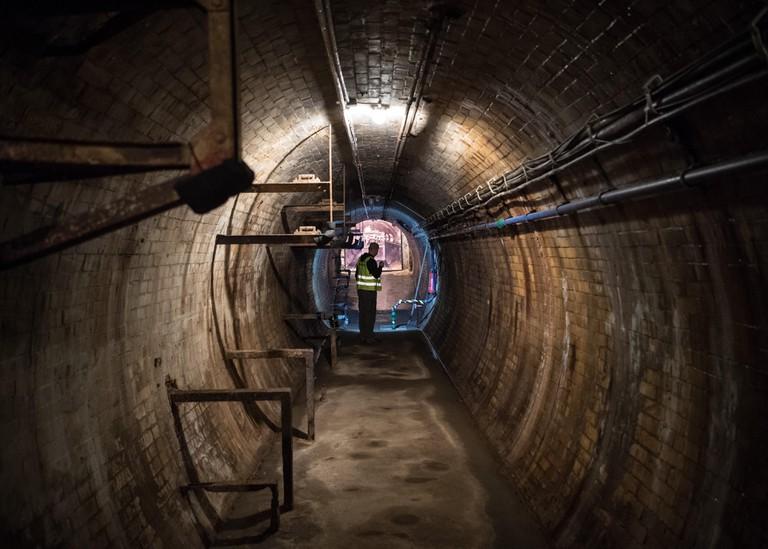 Employee of Berliner Unterwelten in an under ground tunnel in Berlin