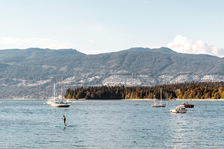 Man paddle boarding on Kitsilano Beach in Vancouver, Canada