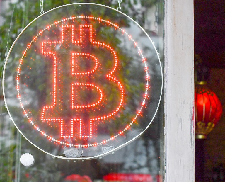 A Bitcoin logo hangs in the shop window of the Bitcoin pub Room 77 in Kreuzberg's Graefekiez