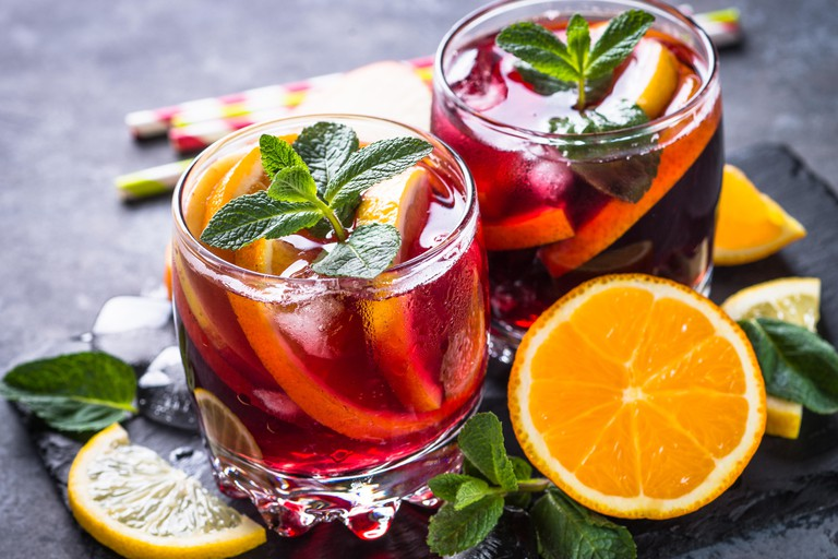 Sangria with fruit, ice and mint in glass.