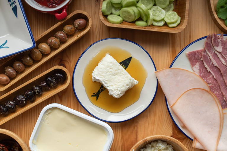 Traditional Turkish Breakfast, eggs with sucuk, bal kaymak, olives, ham, cheese.