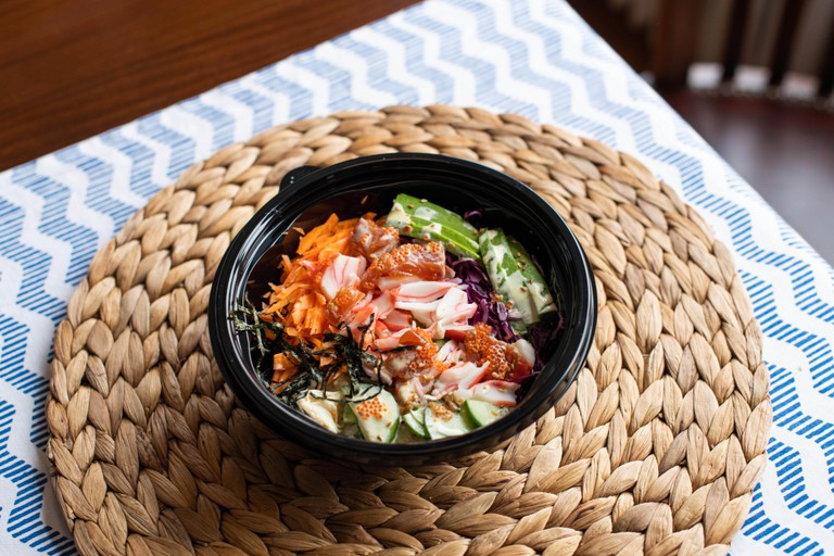 Poke bowl with salmon, rice, surimi, avocado, tobiko, carrot and seaweed