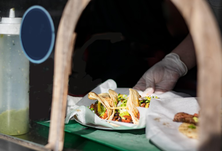 Tacos being served at a taco truck during a food festival