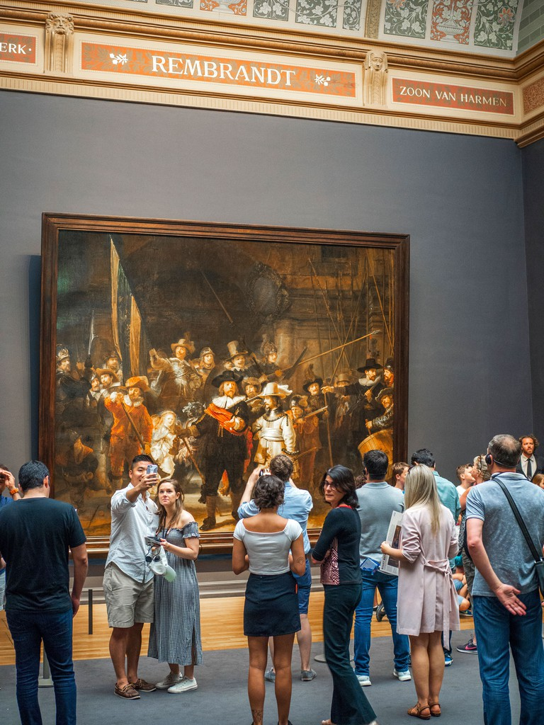 Tourist observing The Night Watch, a painting by Rembrandt Harmenszoon van Rijn, at the Rijksmuseum in Amsterdam, The Netherlands.