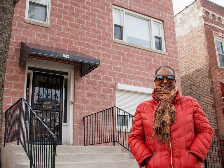 A Folded Map participant standing in front of her Map Twin's home on the North Side of Chicago.