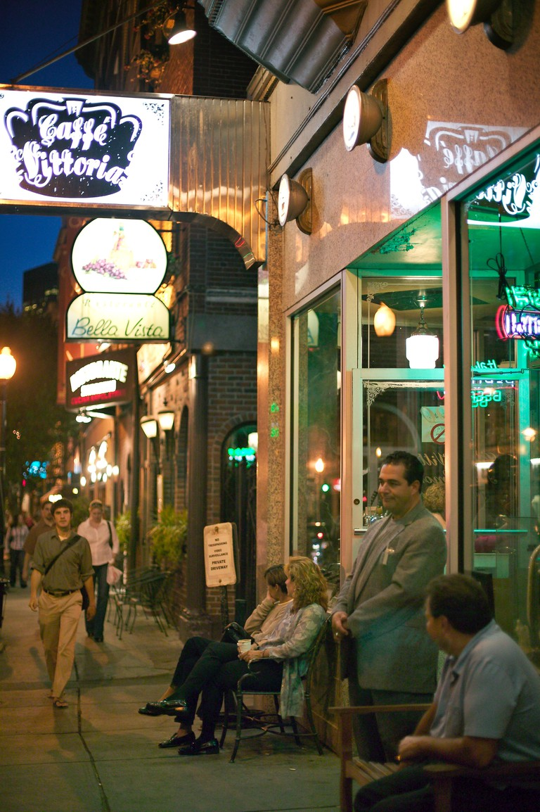 People enjoy evening near Caffe Vittoria on Hanover Street in the Italian District north end Boston MA