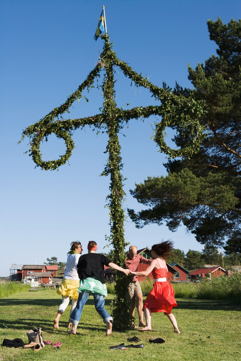 People dancing around the maypole for midsummer Sweden.