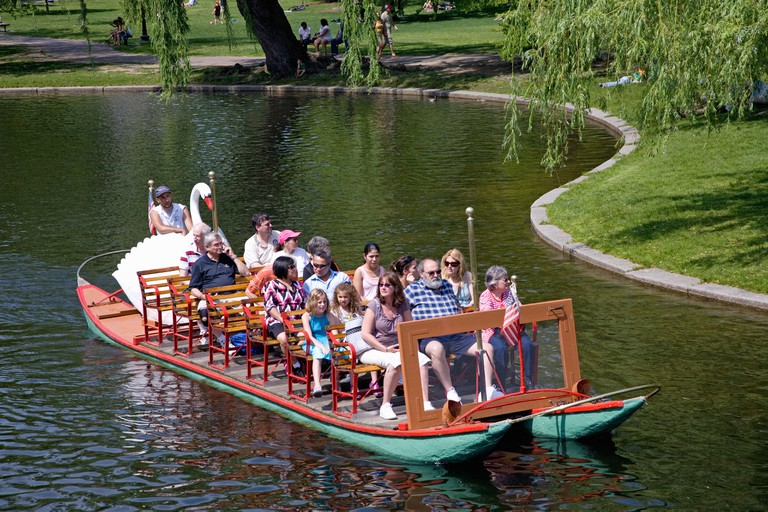 Tourists ride the Historic Swan Boats in Boston Public Gardens on a summer day, Boston, Ma