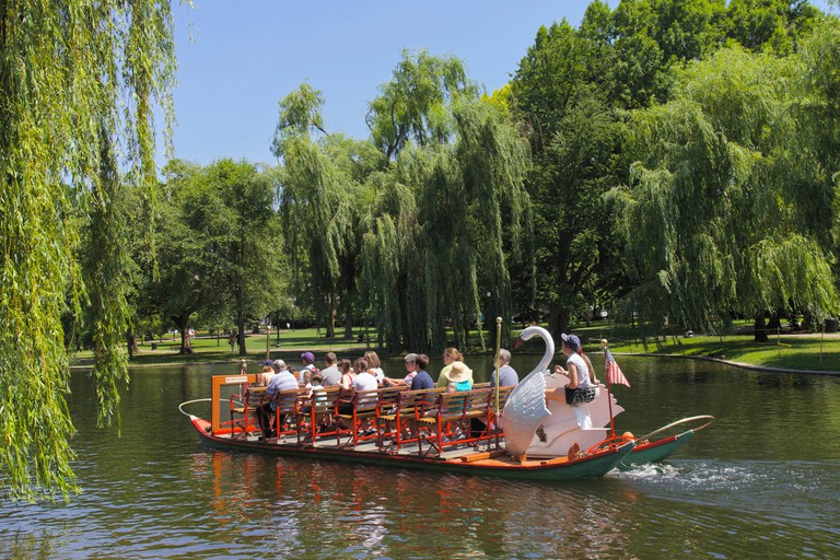 Boston Public Garden and sightseeing tourist on the famous Swan boats in Central Boston, Massachusetts, USA.