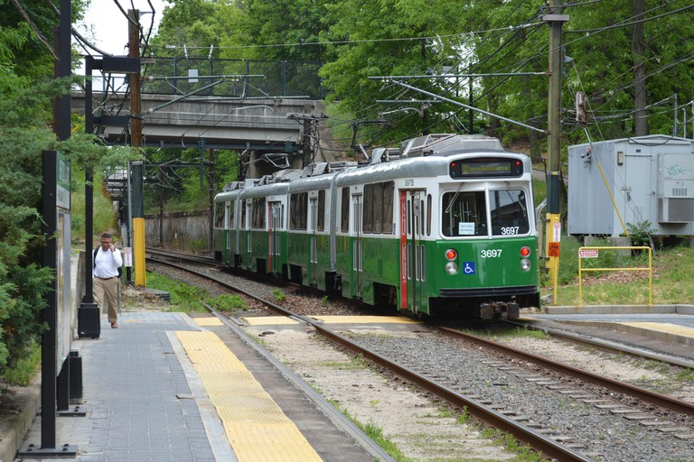 An MBTA light rail vehicle (LRV) or trolley passing through the Newton Centre on Boston's Green Line transit system.