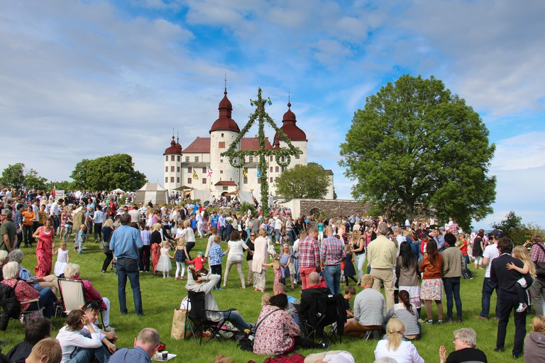 People dancing around the maypole at Lacko Slott (castle) in Sweden