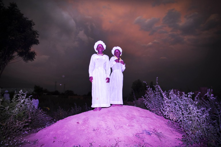 Twins stand on a little monticule at the end of a celebration day at the Celestial Church on a rainy season afternoon