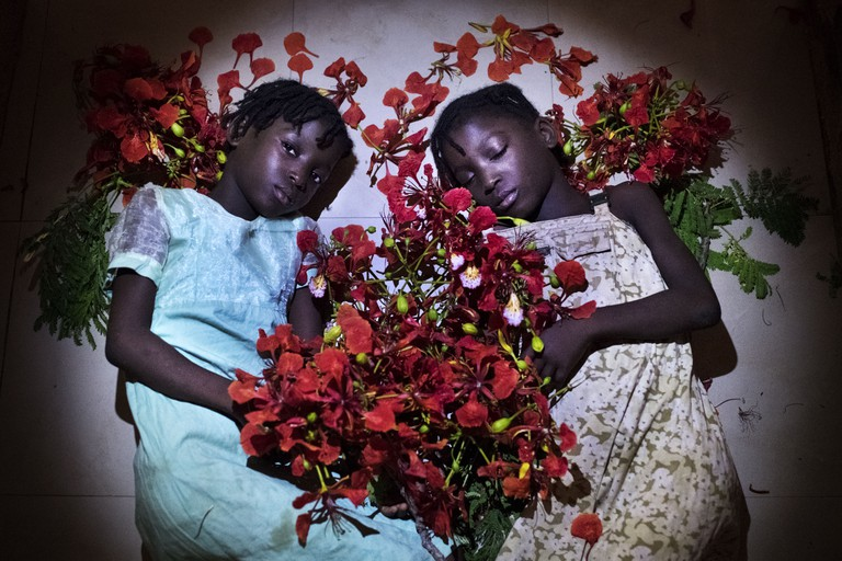 Twins pose for the photographers with local flowers