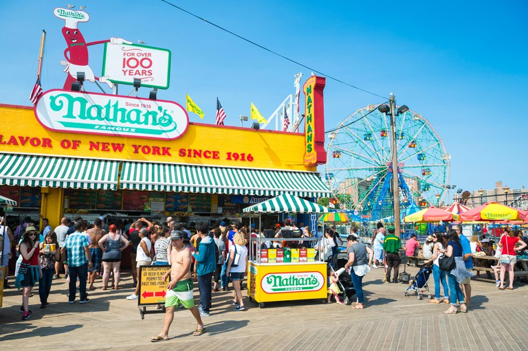 Visitors crowd the iconic wooden Coney Island boardwalk outside the famous Nathan's hot dog stand on a hot summer day