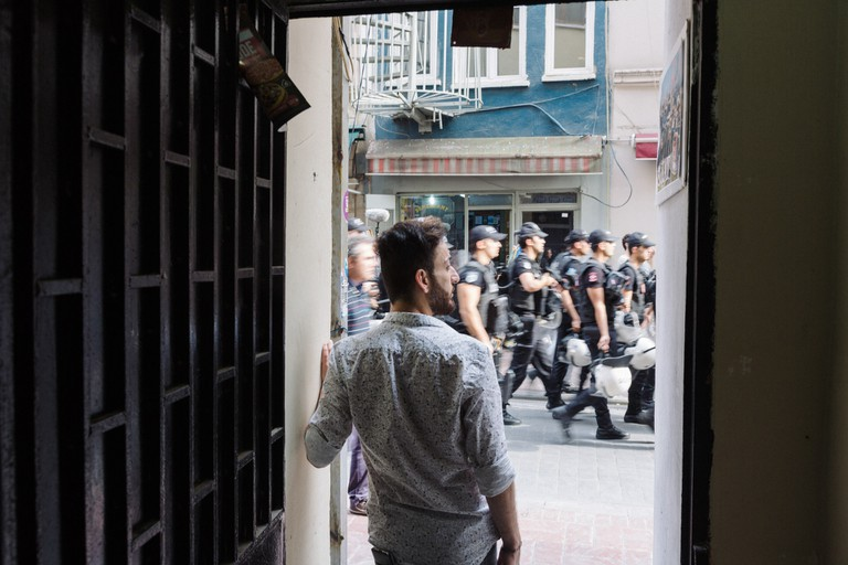 Hussein stands in the doorway of a gay friendly cafe near Mis sokak, as Turkish riot police pass by to prevent the LGBTI Pride march from taking place. Istanbul, Turkey, 26th June 2016.