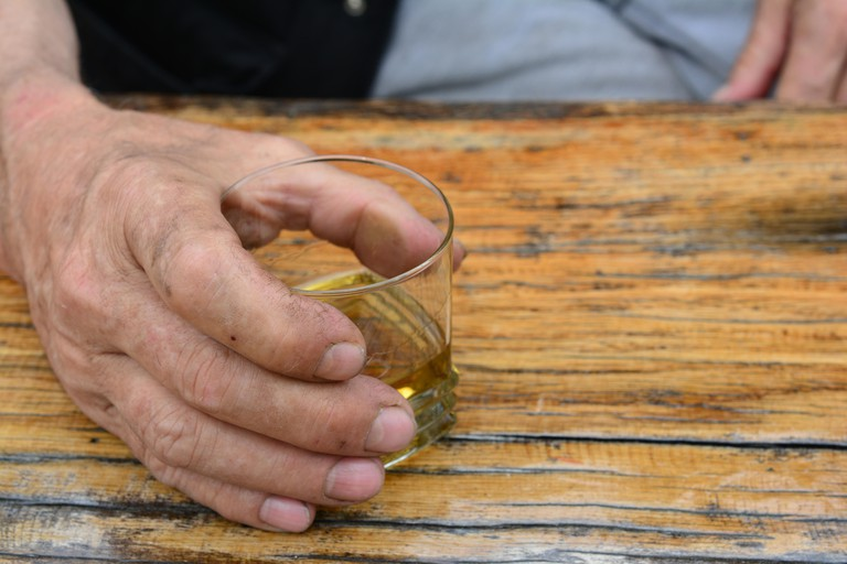 Man's hand holding glass with old, good plum brandy on old, grunge oak table