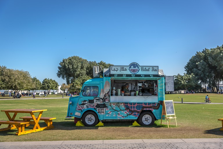 A food truck selling foods and beverages in a public park, green open area, in Doha, Qatar