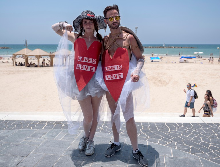 Participants wearing heart-shaped outfits with the words 'Love is Love' pose for a photo on the promenade along the Mediterranean Sea during the Gay Pride Parade in Tel Aviv
