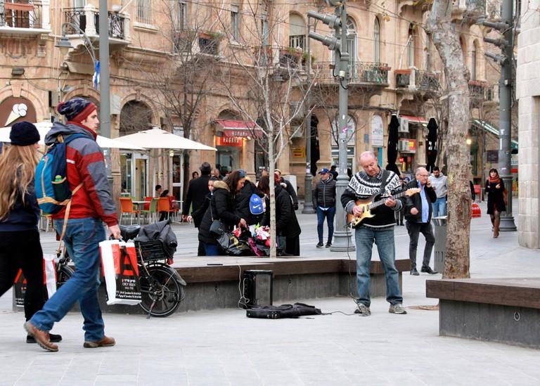 A street musician performs among many pedestrians on Ben Yehudah in Jerusalem.