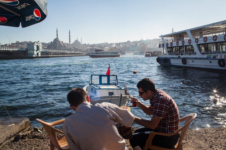Friends drink tea and enjoy the feeling of Keyf on the seafront in Istanbul's Karakoy neighbourhood, Turkey.