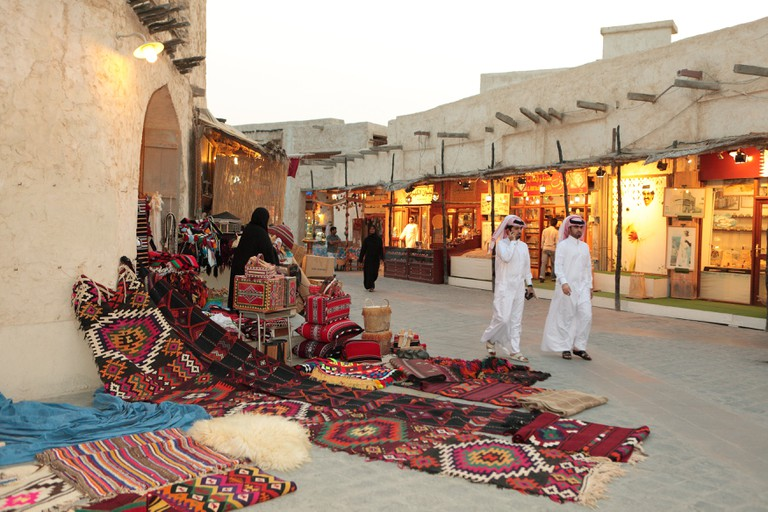 Shoppers outside a traditional textile shop in Souq Waqif, Doha, Qatar, on a quiet evening.