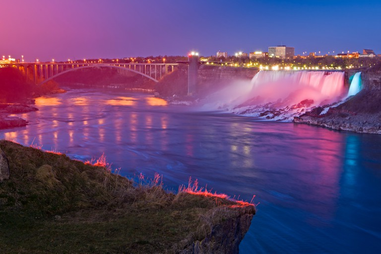 American Falls and the Rainbow Bridge seen from the Canadian side of the Niagara River during the Festival of Lights.
