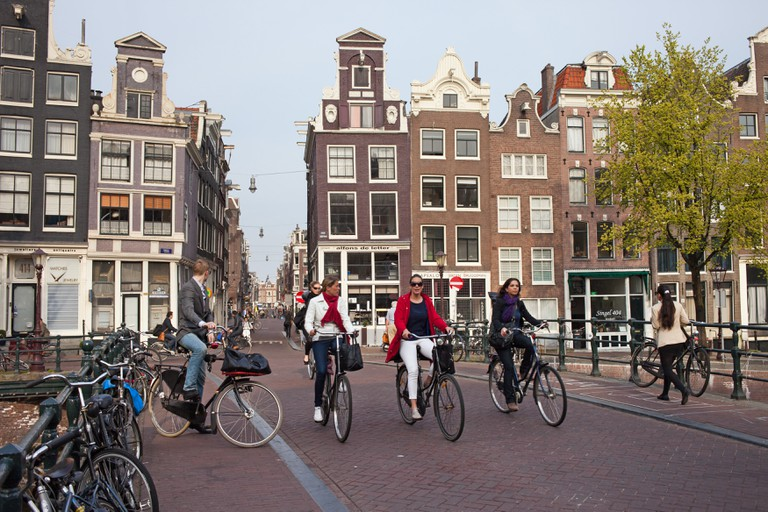 Amsterdammers ride their bicycles over Singel canal bridge in the city of Amsterdam, Netherlands.