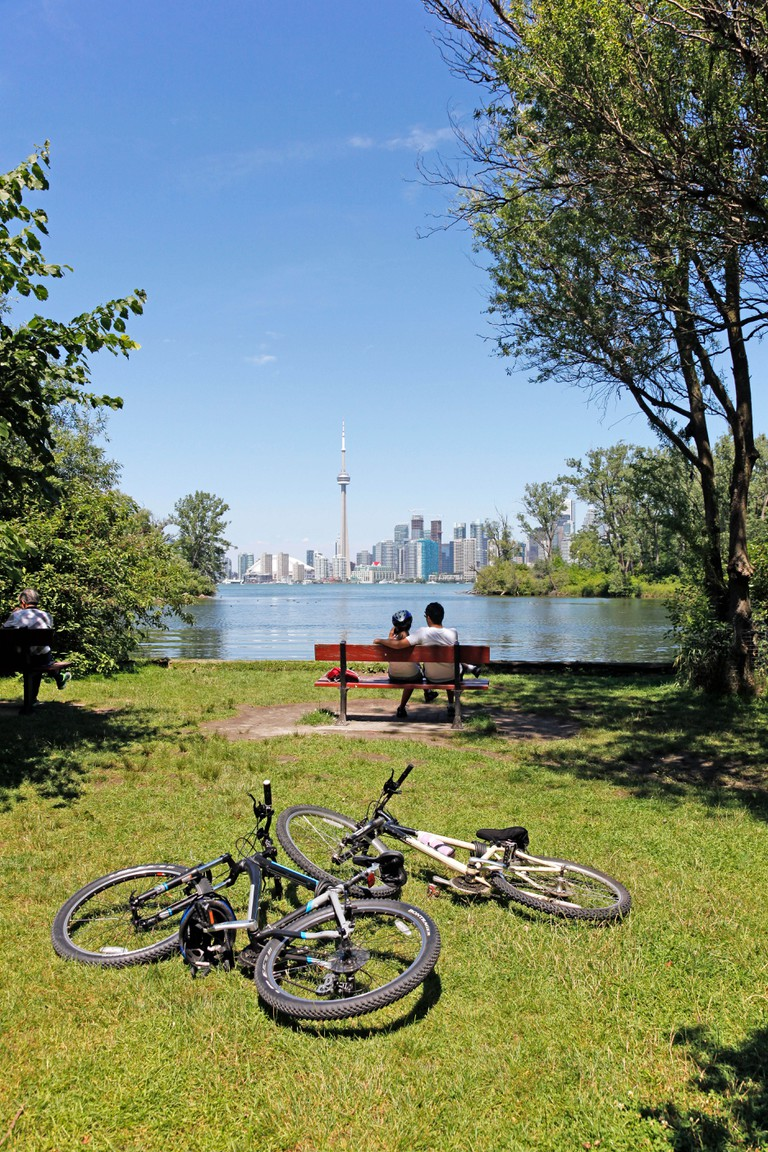 Couple taking in the view after biking to Centre Island Park with Skyline in back ground, Lake Ontario.