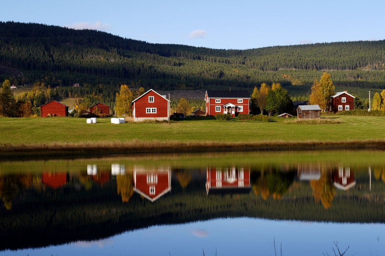 Traditional Swedish countryside houses in Halsingland mirroring in a fresh water lake in the afternoon sun.