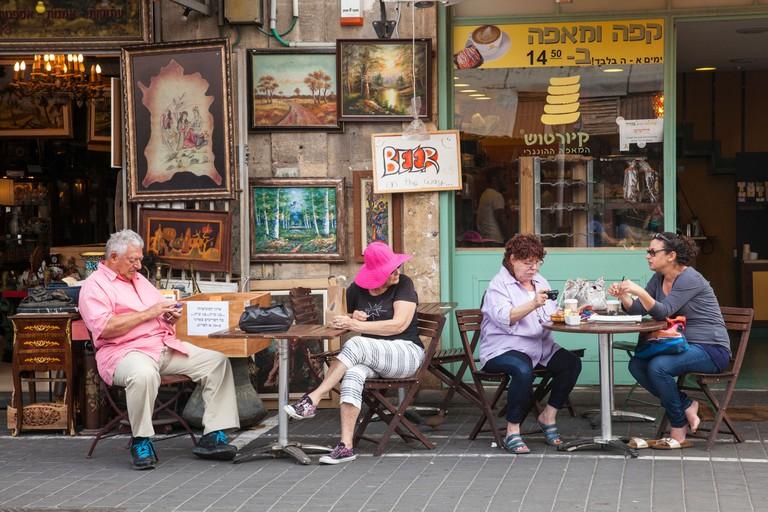 Locals sitting outside a Jaffa coffee shop, in Tel Aviv.
