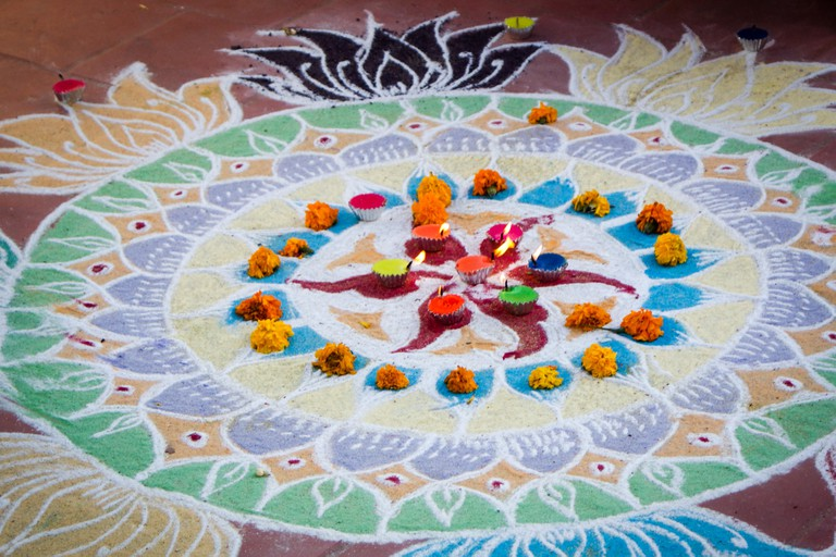 An elaborate kolam with candles
