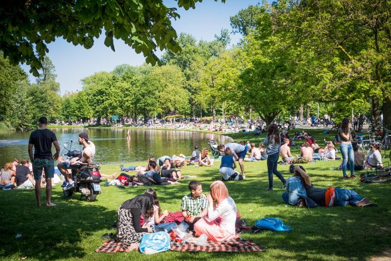 Crowds of people enjoying the sun in Vondelpark, Amsterdam.