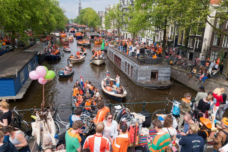 Crowds celebrating Koningsdag, Kings Day Festival in Amsterdam with boats on Prinsengracht Canal and Vrijmarkt on the bridge.