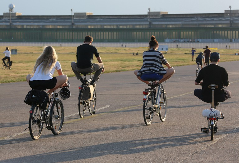 Participants of a YogaCycling course excercise on the Tempelhofer Feld in Berlin, Germany, 11 June 2015. YogaCycling integrates traditional yoga excersises in the daily cycling. Photo: Stephanie Pilick/dpa