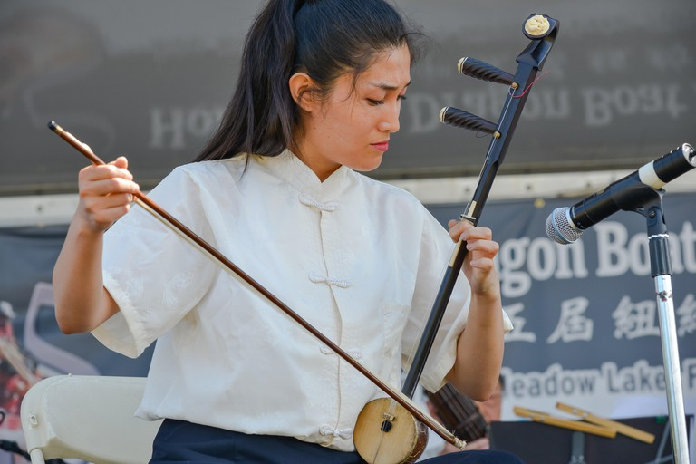 Queens, United States. 08th Aug, 2015. Feifei Yang, performs a traditional Chinese air on a banhu, a type of two-string bowed instrument, during her first performance at the festival.The two-day 25th Annual Hong Kong Dragon Boat Festival was held in Flush