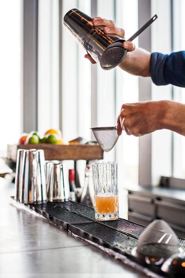 Bartender making cocktail at bar